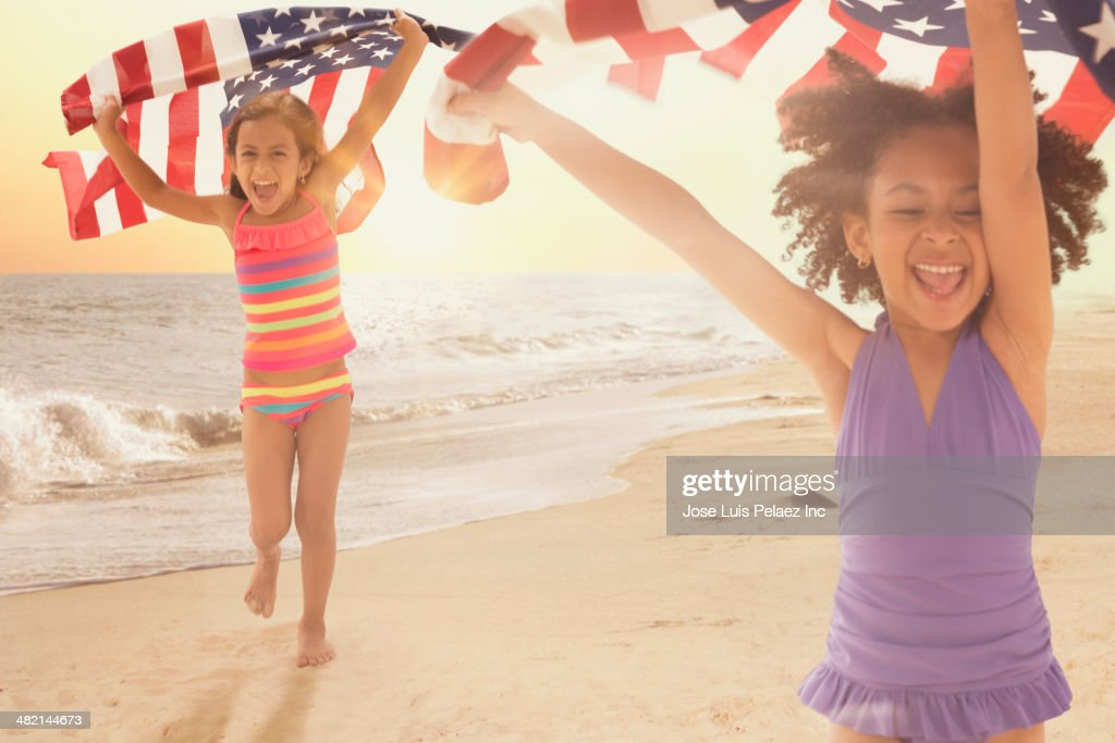 Enthusiastic girls carrying American flags on beach
