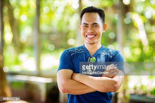 Begeisterte Mitte Erwachsenen indonesischen Mann lächelnd Arme verschränkt im Freien