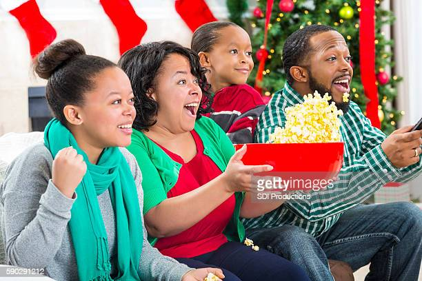 Enthusiastic sports fan watch football game on TV during Christmastime
