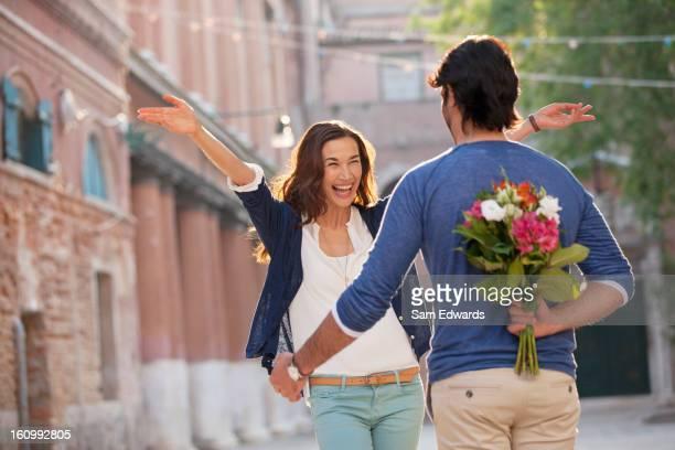 Begeisterte Frau nähern Mann mit Blumen, die hinter dem Rücken