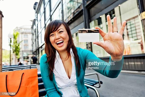 Enthusiastische junge asiatische Frau mit Kreditkarte