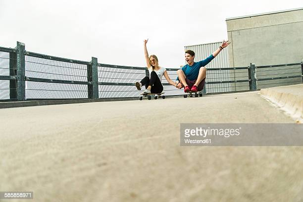 Enthusiastic young couple riding downhill with skateboards