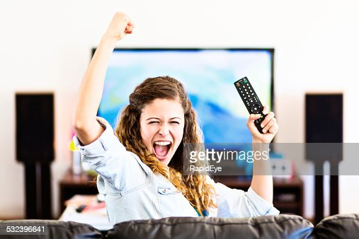 Enthusiastic young female spectator turns from TV cheering triumphantly