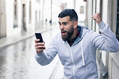 Boy with victorious expression in the city. Overexcited hipster with grey hoodie holding mobile device and fist up. Online bet winner concept