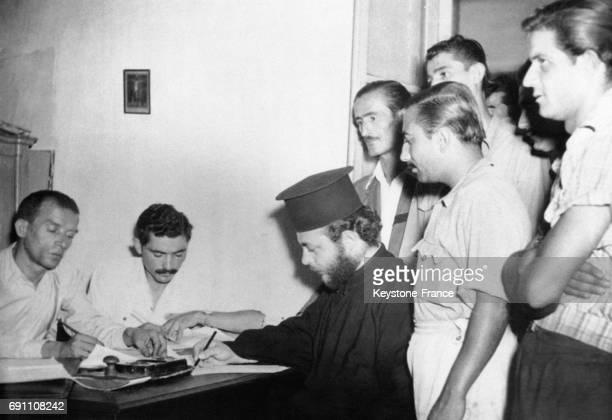 Entouré de jeunes volontaires ce jeune pope de l'église orthodoxe grecque signe sa feuille d'enrôlement pour partir comme prêtre militaire à Athènes...