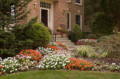 Lush flower beds with impatiens line a walkway to a front door of a residence.