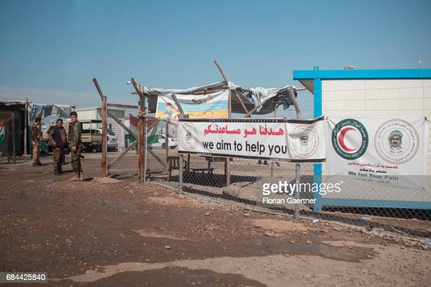 Entrance of a refugee camp A banner with the words 'we aim to help you' is attached to a fence on April 20 2017 in Mosul Iraq