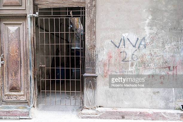 Entrance of an old house with a rusted iron gate Political revolutionary written text on wall reading Live the 26 refering to the 26 of July Movement