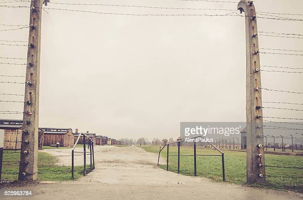 Entrance through electrical fence that surrounds the camp Auschwitz