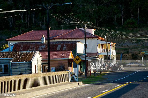 Entrance to town of Whangamomona on Hwy 43 with pub veranda lit by afternoon sunlight.