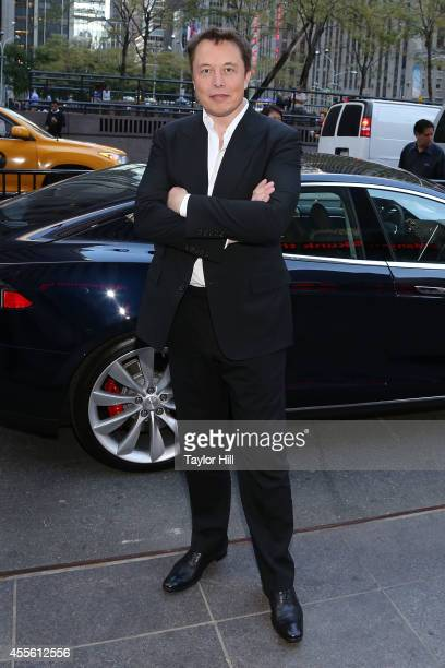 Entrepreneur Elon Musk poses in front of a Tesla outside of 1211 Avenue of the Americas on September 17 2014 in New York City