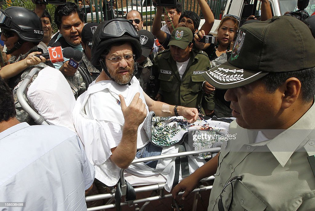 OUT --- US entrepreneur Jacob Ostreicher (C) is carried on a stretcher while exiting a court hearing where the judge granted his liberty in Santa Cruz, Bolivia on December 18, 2012. Ostreicher was detained without charge for 18 months in Palmasola prison, for suspicion of money laundering and criminal organization. AFP PHOTO/STR