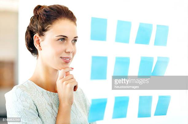 Entrepreneur Looking At Adhesive Notes Stuck On Glass In Office