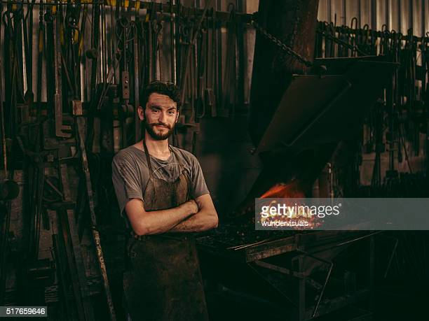 Entrepreneur portrait of blacksmith next to furnace in workshop