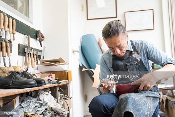 Entrepreneur shoemaker working in his small shoe shop