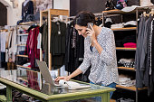 Young businesswoman talking over phone while checking laptop in her clothing store. Young entrepreneur in casual using laptop and talking on mobile. Store manager woman checking important documents on