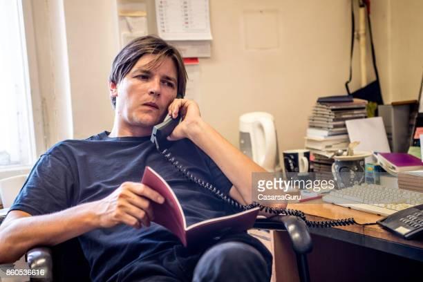 Entrepreneur Talking On Phone In Messy Office