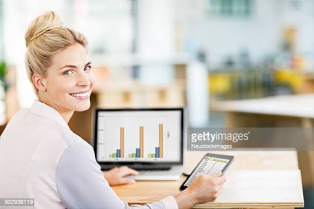 Entrepreneur Using Digital Tablet And Laptop At Desk In Office