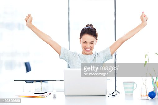 Entrepreneur With Laptop Celebrating Success At Desk