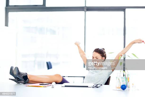Entrepreneur Yawning While Stretching At Office Desk