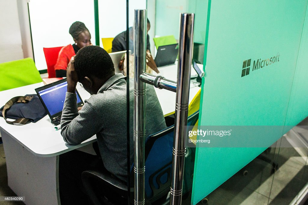 Entrepreneurs work on laptop computers in a glass panelled room displaying a Microsoft Corp. logo inside the m:lab East Africa mobile innovation unit at the i-Hub technology innovation center in Nairobi, Kenya, on Thursday, July 23, 2015. Together, the entrepreneurs come up with concepts like Ushahidi, the open-source software that's used to share information and interactive maps to prevent conflicts and help aid agencies provide relief in disaster zones. Photographer: Waldo Swiegers/Bloomberg via Getty Images