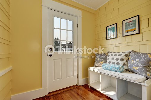 entryway with yellow walls and storage bench in white ストックフォト