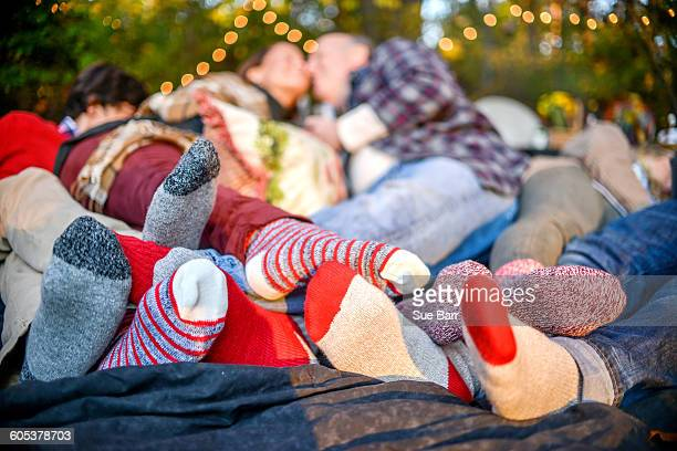 Entwined family socked feet lying on blanket in woods