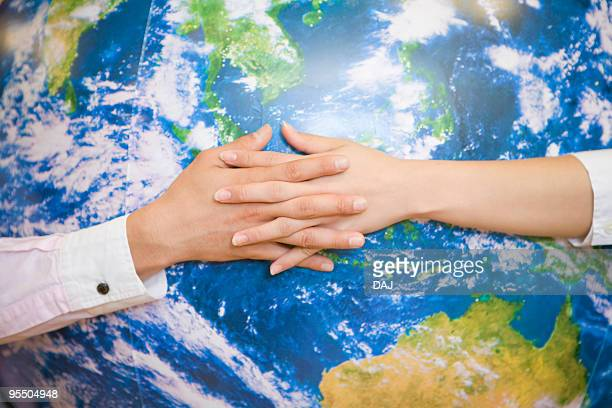 Entwined Hands Reaching Out Across Inflatable Globe