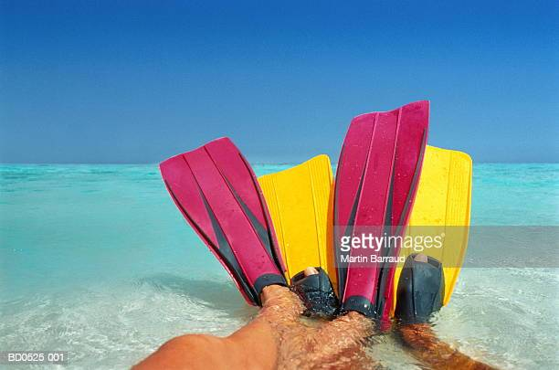 Entwined legs of couple wearing bright flippers on shoreline
