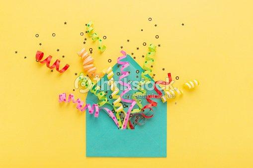 Enveloppe avec explosion de confettis parti sur fond jaune. Carte d'invitation, plat laïc. : Photo