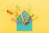 Envelope with party confetti explosion on yellow background. Invitation card, flat lay.