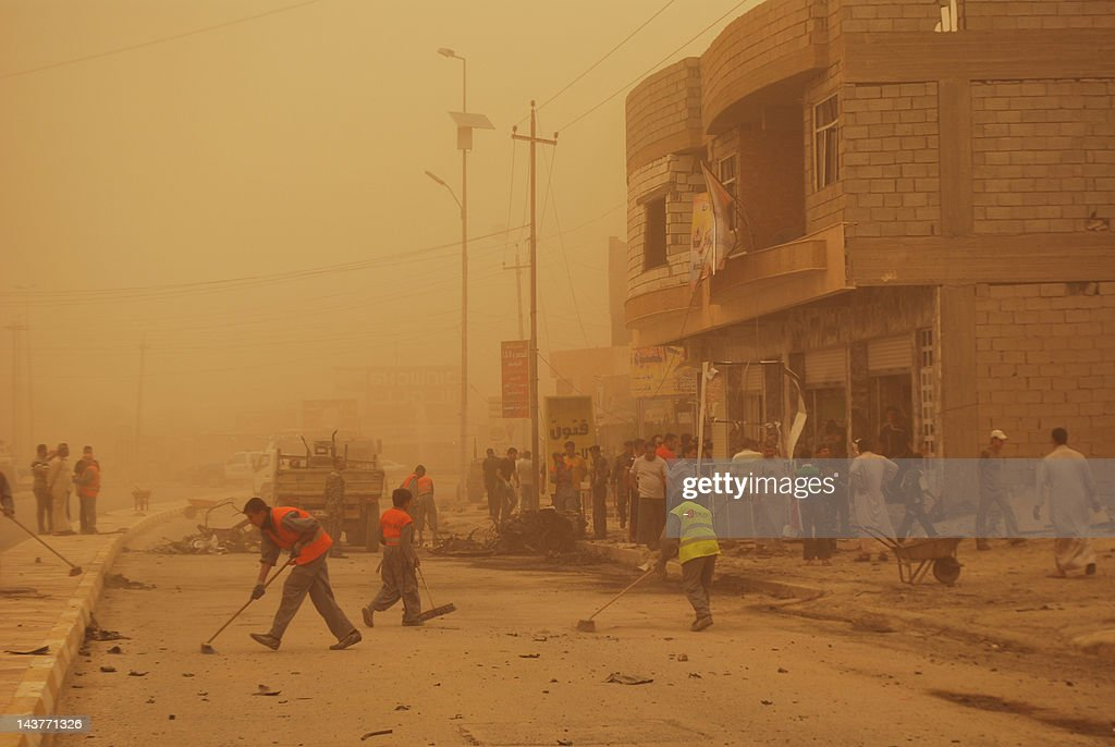 Enveloped by a sand storm Iraqis clear the debris following two car bombs in the western city of Ramadi, in the Anbar province on April 19, 2012, as a wave of bombings and shootings across Iraq killed at least 35 people and wounded dozens more.