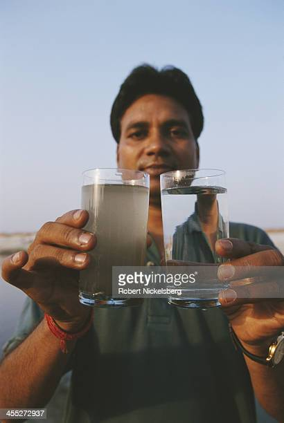 Enviromentalist Rakesh Jaiswal shows a glass of water infected with sewage taken from the Ganges River Canal in Kanpur compared to a glass of mineral...