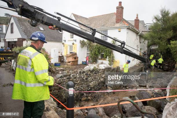Environment Agency workers clear debris from a stream running to the sea in the village of Coverack following flash flooding on July 19 2017 in...