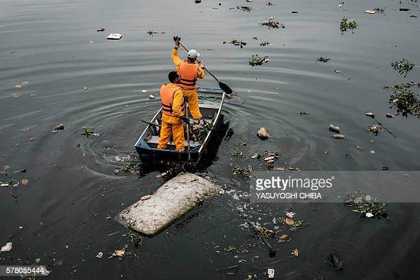 Environment Institute of Rio de Janeiro State staffers collect a bed mattress as the tide moves away from the 'ecobarrier' set up to catch floating...