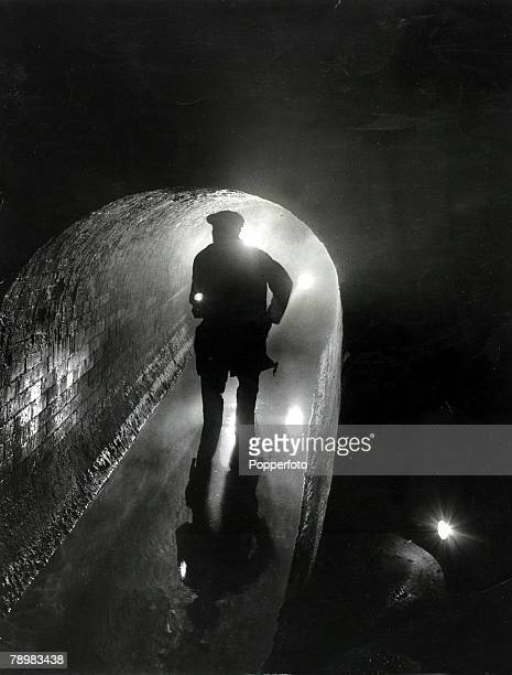 1953 A worker inspecting a dark underground London sewer part of the 3440 miles network underneath London