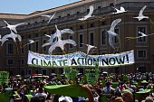 Environmental activists display a banner calling for action on climate change as they arrive on St Peter's square prior to Pope Francis's Sunday...