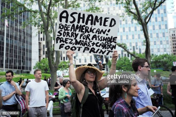 Environmental activists display placards during a demonstration in New York on June 1 to protest US President Donald Trump's decision to pull out of...