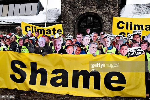 Environmental activists from AVAAZorg carry portraits of world leaders participate in a rally dubbed 'Climate shame' during the last day of the UN...