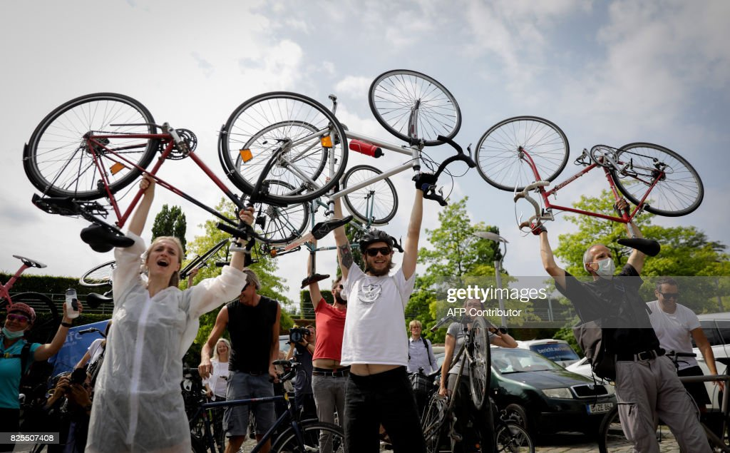 Environmental activists hold up their bikes as they demonstrate on August 2, 2017 in front of the venue of a so-called diesel summit. German government officials and automakers meet in Berlin to discuss the future of diesel vehicles, after a nearly two-year saga of scandal spread from Volkswagen to others in the sector. / AFP PHOTO / DPA / Kay Nietfeld / Germany OUT