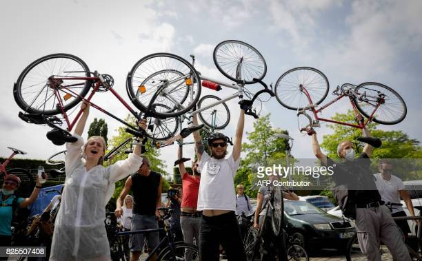 Environmental activists hold up their bikes as they demonstrate on August 2 2017 in front of the venue of a socalled diesel summit German government...