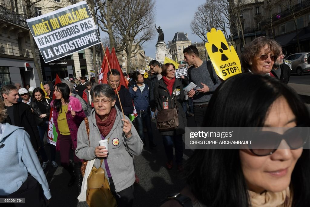 Environmental activists holding a banner reading 'Let's not wait for the disaster !' take part in a demonstration called by Greenpeace and other associations to mark the 6th anniversary of the Fukushima nuclear disaster, on March 11, 2017 in Paris. /