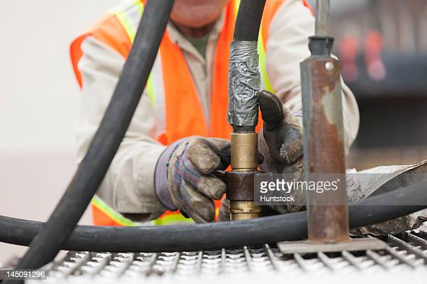 Environmental engineer connecting a coupling on a hose at tanker truck