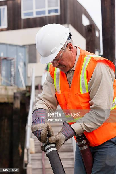 Environmental engineer coupling petroleum hose for toxic waste cleanup on a commercial ship