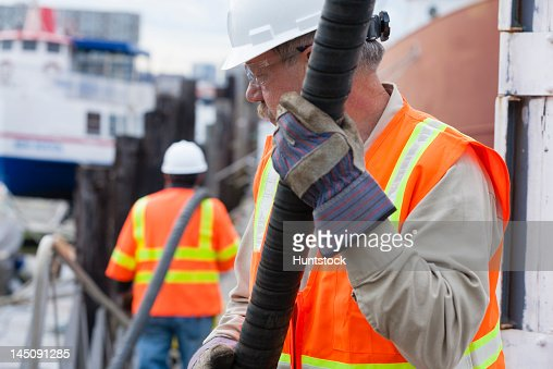 Environmental engineer extending petroleum hose for toxic waste cleanup to commercial ship : Stock Photo