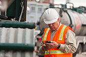 Environmental engineer on cell phone with tank truck at hazardous waste cleanup site