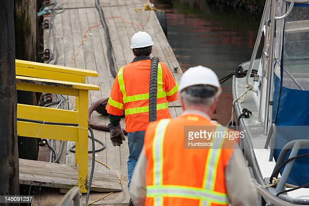 Environmental engineers extending petroleum hose for toxic waste cleanup to commercial ship