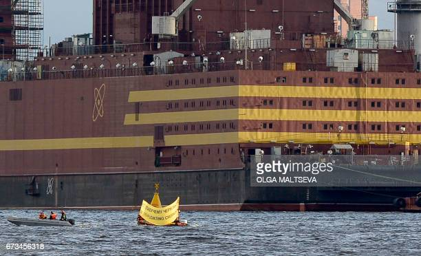 Environmental group Greenpeace activists in a boat display a banner reading 'No To Floating Chernobyl' in front of the floating nuclear power plant...