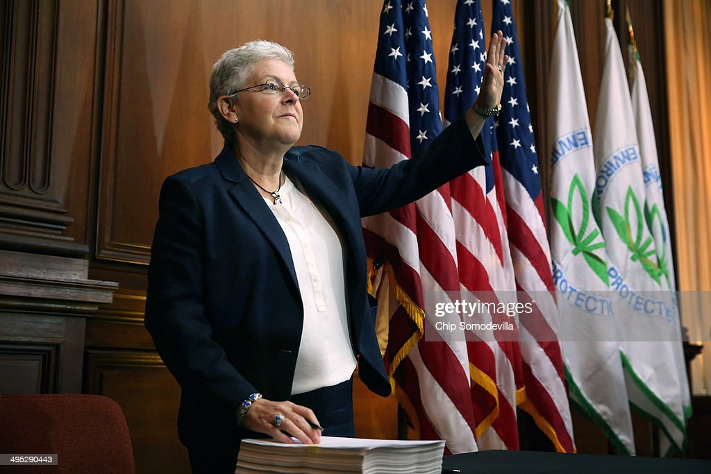 U.S. Environmental Protection Agency Administrator Gina McCarthy waves before signing new regulations for power plants at EPA headquarters June 2, 2014 in Washington, DC. Bypassing Congress and using President Barack Obama's 'Climate Action Plan,' the new regulations will force more than 600 existing coal-fired power plants, the single largest source of greenhouse gas emission in the country, to reduce their carbon pollution 30 percent from 2005 levels by 2030.