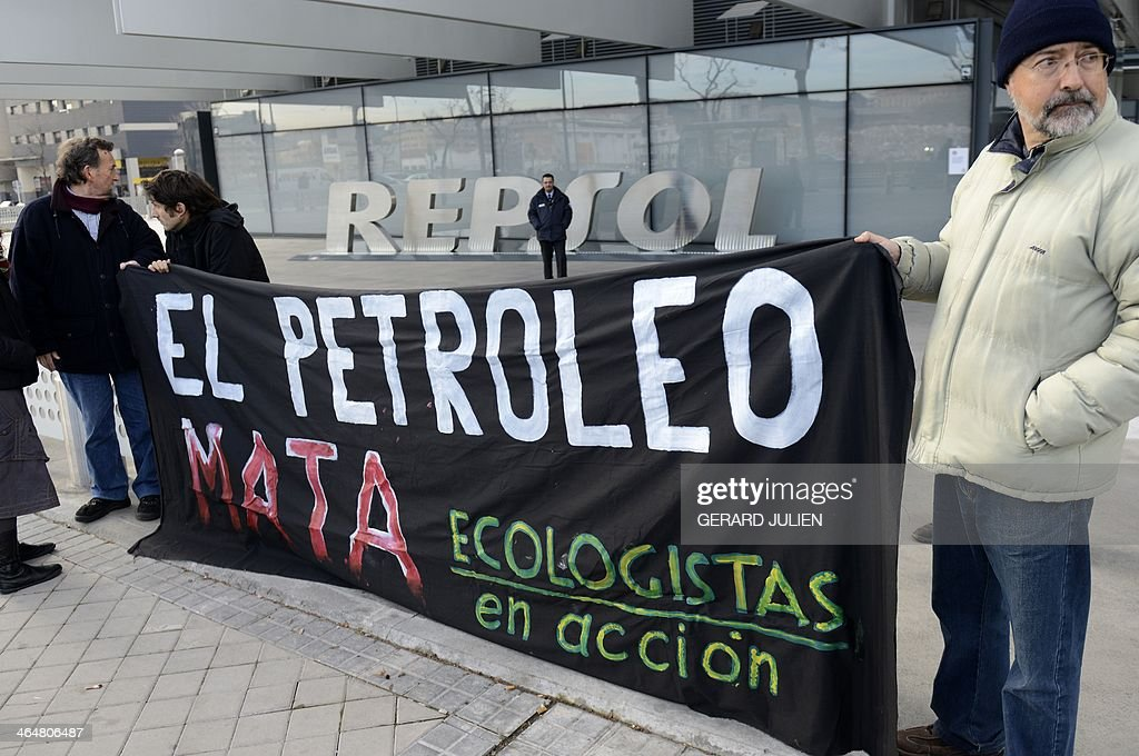 Environmentalist, members of the 'Ecologistas en Accion' NGO, hold a banner reading in Spanish 'Petrol kills' outside the main entrance to Spanish oil giant Repsol's headquarters in Madrid on January 24, 2014 during a symbolic protest action following the release of a report on oil extraction from Canadian tar sands.